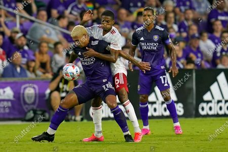 Orlando City midfielder Junior Urso, left, tires to get control of the ball in front of New York Red Bulls defender Kyle Duncan (6) as Orlando City forward Nani (17) looks on during the first half of an MLS soccer match, in Orlando, Fla