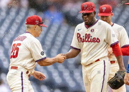 Philadelphia Phillies relief pitcher Hector Neris, front right, gives the ball to manager Joe Girardi (25) after coming off the mound during the ninth inning of a baseball game against the San Diego Padres, in Philadelphia