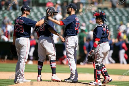 Stock Image of Boston Red Sox pitcher Matt Barnes (32) and teammates first baseman Bobby Dalbec (29), third baseman Rafael Devers (11) and catcher Christian Vázquez (7) celebrate their 1-0 victory over the Oakland Athletics in a baseball game, in Oakland, Calif