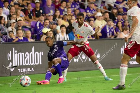 Nani (17 Orlando City) holds onto Kyle Duncan (6 New York Red Bulls) as he falls after making a pass during the Major League Soccer game between Orlando City and New York Red Bulls at Exploria Stadium in Orlando, Florida.