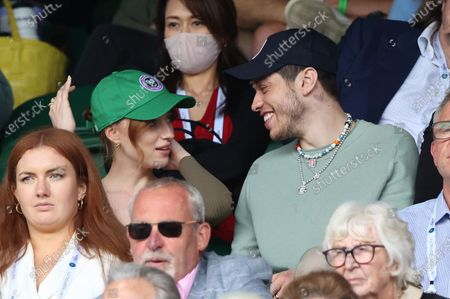 Stock Image of Phoebe Dynevor puts on a cap alongside Pete Davidson watching Federer v Norrie in the third round.