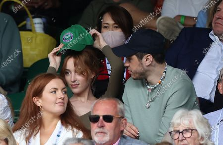 Stock Photo of Phoebe Dynevor puts on a cap alongside Pete Davidson watching Federer v Norrie in the third round.