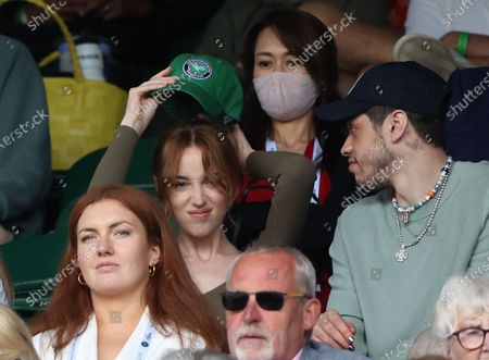 Phoebe Dynevor puts on a cap alongside Pete Davidson watching Federer v Norrie in the third round.