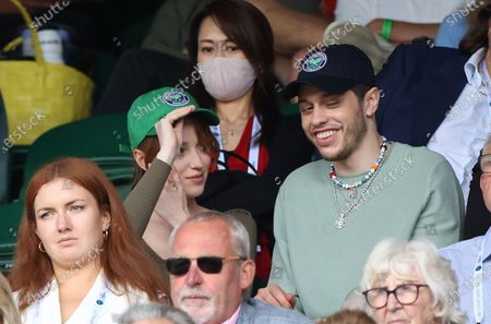 Stock Picture of Phoebe Dynevor puts on a cap alongside Pete Davidson watching Federer v Norrie in the third round.
