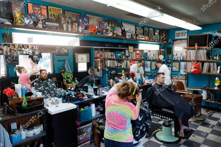 Musical memorabilia line the walls and shelves of the Glory Days Corner Barber Shop as Katie Hennenfent, left, cuts Ryan Hardwell's hair and as Sam Carr, right, attends to Jack Dechow in Galesburg, Ill