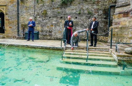 Prince Charles (second right) touches the healing water during a visit to St Winefride's Well, Flintshire, north Wales, as Lord-Lieutenant of Clwyd, Henry Fetherstonhaugh (left), Bishop of Wrexham Peter Brignall (second left) and Roman Catholic parish Priest for Holywell, Father Justin Karakadu (right) look on, at the popular Catholic pilgrimage site, as part of a week long tour of Wales for Wales Week.