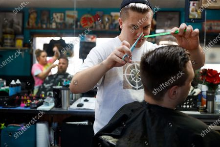 Stock Photo of Barber Sam Carr 23, cuts the hair of fellow Galesburg, Ill., resident Jack Dechow, 23, at the Glory Days Corner Barber Shop in Galesburg