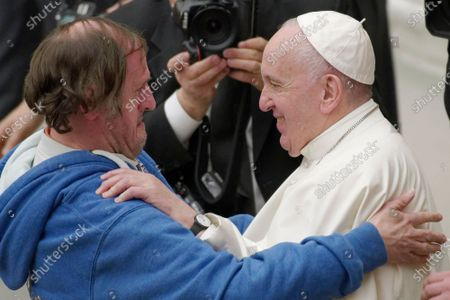 Pope Francis is hugged by a man during his weekly general audience, at the Pope Paul VI hall, at the Vatican, Wednesday, Feb. 19, 2020.