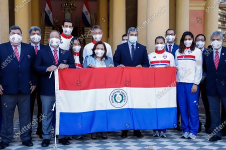 Stock Photo of The President of Paraguay, Mario Abdo Benitez (C-R), and the Minister of Sports Fatima Morales Aguero (C-L), pose with the Paraguayan athletes qualified for the Tokyo Olympics at the Government Palace in Asuncion, Paraguay, 05 July 2021. President of Paraguay Mario Abdo Benitez presented this 05 July to the delegation of Paraguayan athletes qualified for the Tokyo Olympic Games the flag that they will wave during the inaugural parade of the sports event.