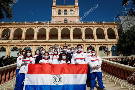 (Down, L-R) The 100-meter hurdles athlete Camila Pirelli, swimmer Luana Alfonso, tennis player Veronica Cepede, and swimmer Bejamin Hockin, pose with other Paraguayan athletes qualified for the Tokyo Olympics at the Government Palace in Asuncion, Paraguay, 05 July 2021. President of Paraguay Mario Abdo Benitez presented this 05 July to the delegation of Paraguayan athletes qualified for the Tokyo Olympic Games the flag that they will wave during the inaugural parade of the sports event.