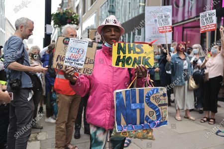 Stock Image of A participant seen holding placards to show support to the NHS during the demonstration.A group of NHS supporters gathered outside the Department of Health and Social Care at the 73rd Anniversary of the NHS to protest against the government's strategies on trying to privatize the healthcare service in the UK. Jeremy Corbyn was in appearance to show support to the NHS service.