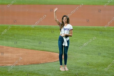 Paige Vasquez, Miss Texas, acknowledges cheers from fans before throwing out the ceremonial first pitch before a baseball game between the Detroit Tigers and the Texas Rangers in Arlington, Texas