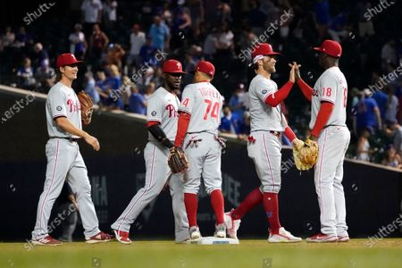 The Philadelphia Phillies from left, Luke Williams, Odubel Herrera, Ronald Torreyes, Bryce Harper and Didi Gregorius celebrate the team's 13-3 win over the Chicago Cubs after a baseball game, in Chicago