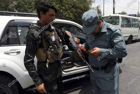 An Afghan policeman checks the documentation of a gun owner, at a temporary checkpoint in Kabul, Afghanistan, . Long before the last U.S. and NATO troops packed up to leave Afghanistan, American diplomats arriving in the capital Kabul were taken to the heavily fortified U.S. Embassy by helicopter. The short four- mile road trip through Kabul's chaotic traffic was considered too dangerous