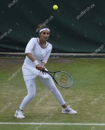 India's Sania Mirza plays a return to Jean-Julien Rojer from the Netherlands and Slovenia's Andreja Klepac during the mixed doubles third round match on day eight of the Wimbledon Tennis Championships in London