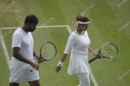 India's Sania Mirza and Rohan Bopanna walks off the court as rain suspends play during the mixed doubles third round match against Jean-Julien Rojer from the Netherlands and Slovenia's Andreja Klepac on day eight of the Wimbledon Tennis Championships in London