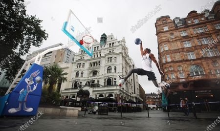 Stock Picture of To celebrate the release of Space Jam: A New Legacy in cinemas on 16th July, young basketball players from charitable organisation Who's Got Game and sports presenter Radzi Chinyanganya unveil the new look Bugs Bunny statue in Leicester Square, part of the long-term Scenes in the Square sculpture trail. The dynamic sculpture now includes a life-sized basketball and hoop, along with a decorative floral display in the colours of the Tune Squad, as well as interactive space Jam lenses through a QR code.