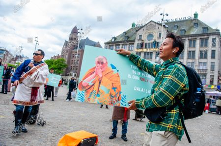 A Tibetan man is holding a placard with the portrait of Dalai Lama on it, during the Dalai Lama 86th birthday celebration in Amsterdam, on July 6th, 2021.