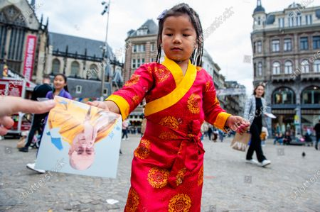 A little Tibetan girl is giving flyers with the Dalai Lama portrait of them to the people at the square, during the Dalai Lama 86th birthday celebration in Amsterdam, on July 6th, 2021.