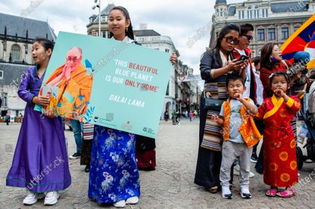 A Tibetan woman is holding a placard with the portrait of Dalai Lama on it, during the Dalai Lama 86th birthday celebration in Amsterdam, on July 6th, 2021.