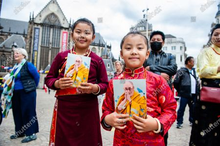 Two Tibetan girls are holding flyers with the portrait of Dalai Lama, during the Dalai Lama 86th birthday celebration in Amsterdam, on July 6th, 2021.