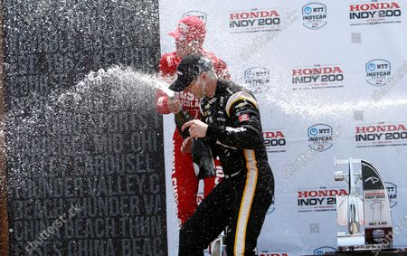 Josef Newgarden gets sprayed with champagne by Marcus Ericsson in victory lane after winning the IndyCar race at Mid-Ohio Sports Car Course in Lexington, Ohio