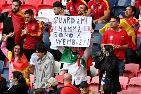 """An Italy supporter among Spain fans holds up a poster with the words in Italian """"Look at me mom, I'm at Wembley"""" on the stands before the Euro 2020 soccer championship semifinal match between Italy and Spain at Wembley stadium in London"""