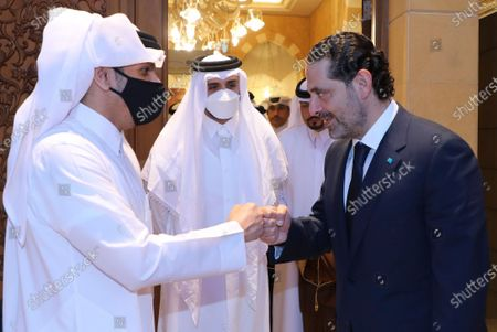 In this photo released by Lebanon's official government photographer Dalati Nohra, Lebanese Prime Minister-Designate Saad Hariri, right, greets with a fist bump Qatar's Deputy Prime Minister and Foreign Minister Sheikh Mohammed bin Abdulrahman bin Jassim Al-Thani, as he welcomes him at his house, in Beirut, Lebanon, . Qatar's Foreign Minster is in Beirut for one day visit to meet with Lebanese officials and the Lebanese Army Commander Gen. Joseph Aoun