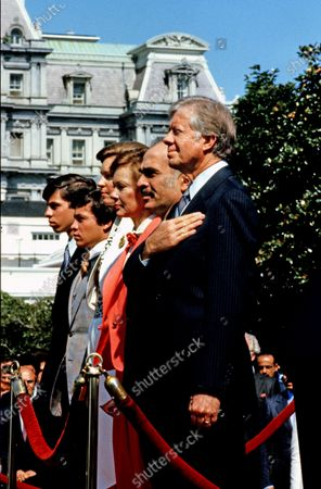 United States President Jimmy Carter, right, King Hussein I of Jordan, second right, and first lady Rosalynn Carter, third right, stand at attention as the National Anthem is performed during a State Arrival ceremony on the South Lawn of the White House in Washington, DC on 17. Also pictured are King Hussein's sons Abdullah II bin Al-Hussein, second left and Prince Faisal bin Hussein, left.