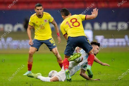Stock Photo of Argentina's Nicolas Tagliafico falls under Colombia's Rafael Santos Borre during a Copa America semifinal soccer match at the National stadium in Brasilia, Brazil