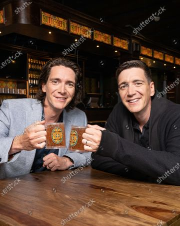 James and Oliver Phelps, who played Fred and George Weasley in the Harry Potter film series, enjoy a bottle of Butterbeer in London's only bottled Butterbeer bar. The bar opens as part of The Harry Potter Photographic Exhibition on July 12th in Covent Garden.