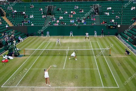 Stock Photo of India's Sania Mirza and Rohan Bopanna, back, play the mixed doubles third round match against Jean-Julien Rojer from the Netherlands and Slovenia's Andreja Klepac on day nine of the Wimbledon Tennis Championships in London