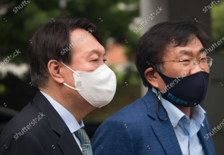 South Korean former Prosecutor General Yoon Seok-Youl (L), who has announced his intention to run in next year's presidential election as an opposition candidate, arrives with professor Joo Han-Kyu to attend a press conference at Seoul National University. South Korean President Moon Jae-In selected Yoon in July 2019 to lead the national prosecution service but Yoon later clashed with president Moon government's justice ministers over a prosecution reform drive which was one of Moon's major presidential election pledges. Yoon stepped down as prosecutor general in early March 2021. Yoon is one of leading candidates for the next presidential election of South Korea.