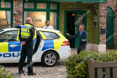 Stock Photo of Coronation Street - Ep 10377 Wednesday 14th July 2021 - 2nd Ep Billy Mayhew and Todd Grimshaw watch as Craig Tinker, as played by Colson Smith, manhandles an angry Paul Foreman, as played by Peter Ash, into a police car.