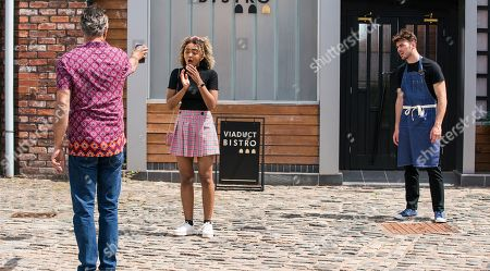 Coronation Street - Ep 10384 & Ep 10385 Friday 23rd July 2021  Dev Alahan, as played by Jimmi Harkishin, brandishes the calendar picture at Curtis, as played by Sam Retford, and Emma Brooker, as played by Alexandra Mardell, and demands they put a stop to the print run.