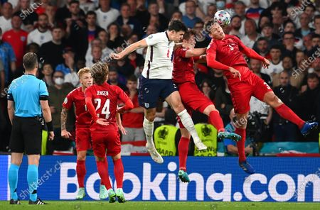 Harry Maguire (C) of England in action against Jannik Vestergaard (R) of Denmark during the UEFA EURO 2020 semi final between England and Denmark in London, Britain, 07 July 2021.