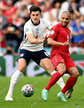 England's Harry Maguire, left, challenges Denmark's Martin Braithwaite during the Euro 2020 soccer championship semifinal match between England and Denmark at Wembley Stadium in London