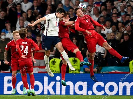 England's Harry Maguire, center, challenges Denmark's Jannik Vestergaard, right, during the Euro 2020 soccer championship semifinal match between England and Denmark at Wembley Stadium in London