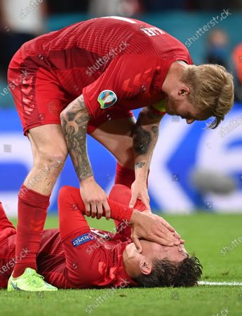 Denmark's Simon Kjaer, up, checks on Denmark's Jannik Vestergaard during the Euro 2020 soccer championship semifinal match between England and Denmark at Wembley Stadium in London
