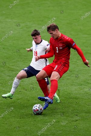 England's Mason Mount vies for the ball with Denmark's Jannik Vestergaard, right, during the Euro 2020 soccer championship semifinal match between England and Denmark at Wembley stadium in London