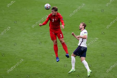Denmark's Jannik Vestergaard heads the ball next to England's Harry Kane, right, during the Euro 2020 soccer championship semifinal match between England and Denmark at Wembley stadium in London