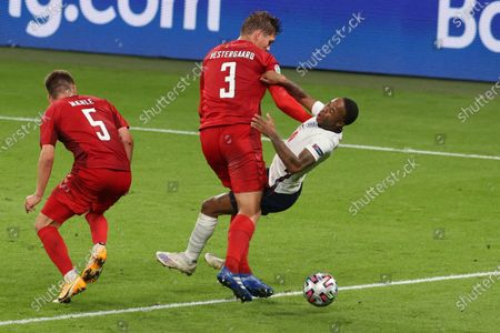 England's Raheem Sterling, right, falls down in a clash with Denmark's Jannik Vestergaard during the Euro 2020 soccer championship semifinal match between England and Denmark at Wembley stadium in London