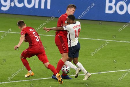 England's Raheem Sterling, right, collides with Denmark's Jannik Vestergaard during the Euro 2020 soccer championship semifinal match between England and Denmark at Wembley stadium in London