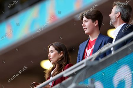 Stock Photo of Mary, Crown Princess of Denmark, looks from the stands with her son Prince Christian and husband Crown Prince Frederik, right, before the Euro 2020 soccer championship semifinal match between England and Denmark at Wembley stadium in London