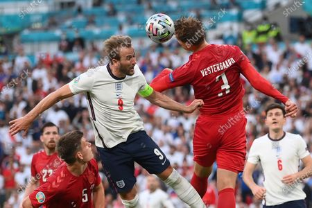 England's Harry Kane, left, jumps for the ball with Denmark's Jannik Vestergaard during the Euro 2020 soccer semifinal match between England and Denmark at Wembley stadium in London