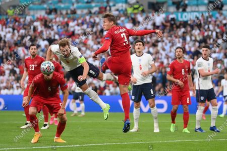 England's Harry Kane, second left, jumps for the ball with Denmark's Joakim Maehle, left, and Denmark's Jannik Vestergaard during the Euro 2020 soccer semifinal match between England and Denmark at Wembley stadium in London