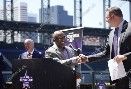 Denver Mayor Michael Hancock, center, shakes hands with Reed Saunders, public address announcer at Coors Field, as Richard Scharf, left, VISIT Denver president and chief executive officer, looks on during a news conference to kick off All-Star week at Coors Field in Denver