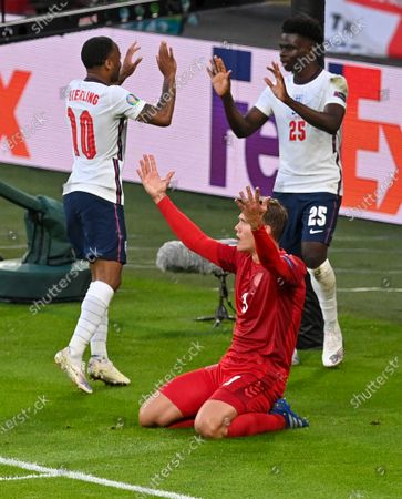 England's Raheem Sterling and teammate Bukayo Saka, right, celebrate after their first goal as Denmark's Jannik Vestergaard reacts during the Euro 2020 soccer championship semifinal between England and Denmark at Wembley stadium in London