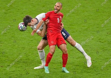 England's Harry Maguire and Denmark's Martin Braithwaite, right, battle for the ball during the Euro 2020 soccer championship semifinal between England and Denmark at Wembley stadium in London