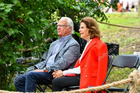 Stock Picture of Queen Silvia and King Carl Gustaf of Sweden in the audience during Solliden sessions concert with Swedish artist Peter Joback at Solliden Palace in Borgholm